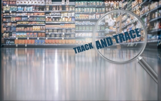 """""""track and trace"""" text magnified with magnifying glass in a supermarket"""